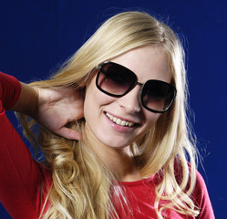 Sexy woman wearing sunglasses against blue background