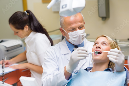 Dentist doing procedure on young patient woman