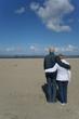 Seniorenpaar am Strand blickt auf das Meer