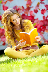 Portrait of a gorgeous brunette woman reading a book in the autu