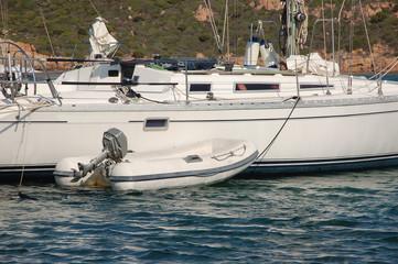 tratto di barca ormeggiato con tender al seguito