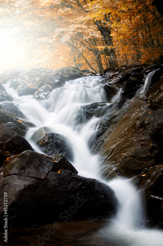 waterfall on  river through forest in autumn