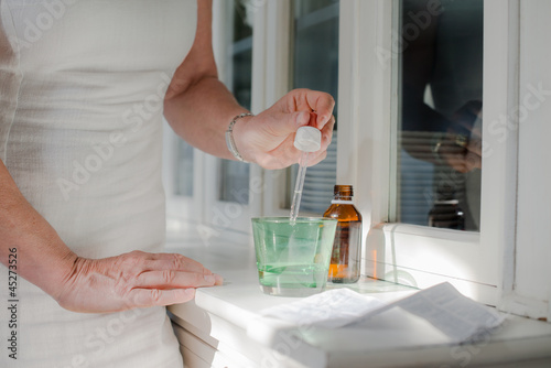 Health issues, old woman taking prescription drugs and drinking
