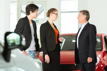 Älterer Mann mit Autos und jungem Pärchen im Autohaus