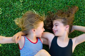 sisters kid girls smiling lying on garden grass