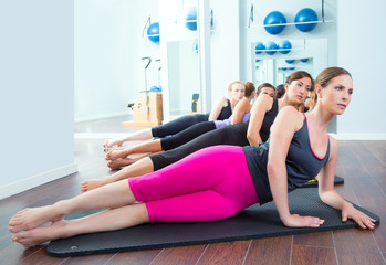 Pilates women group lying on mat with gym instructor