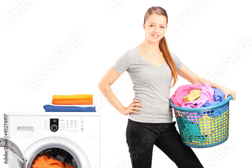 Woman holding a laundry basket next to a washing machine