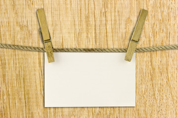 paper hang on clothesline with clipping path on wood background