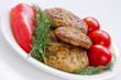 Fried meatballs with dill and tomatoes on a plate
