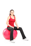 Portrait of a young female sitting on a pilates ball