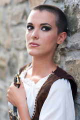 Beautiful girl wearing a medieval dress. Stone wall background.