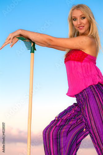 Smiling pretty blonde gardener with gardening tool