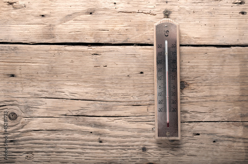 old thermometer on a wooden background