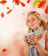 Conceptual autumn portrait of beautiful blond woman drinking tea