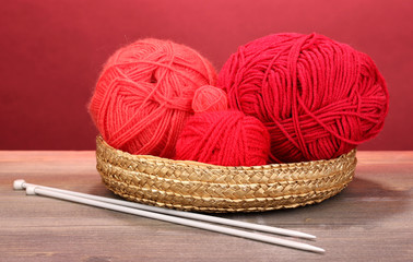 Red knittings yarns in basket on wooden table on red background