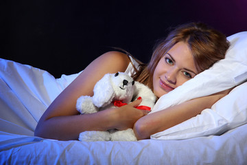 young beautiful woman with toy rabbit lying on bed in bedroom