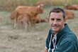 Herdsman standing in front of cattle in farm