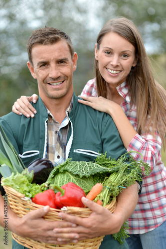 Portrait of couple of farmers holding basket of vegetables