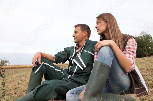 Couple of farmers sitting outside in field