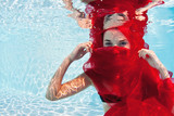 Underwater woman fashion portrait with red veil in swimming pool
