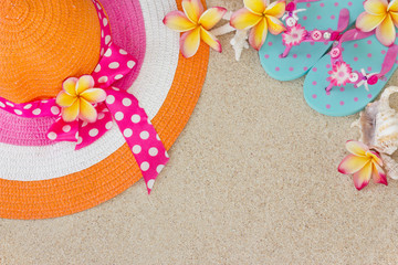 Hat and Flip Flops in the sand with shells and frangipani flower