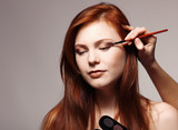Portrait of beautiful young redheaded woman with esthetician mak poster