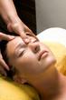 Portrait of a beautiful brunette woman taking head massage