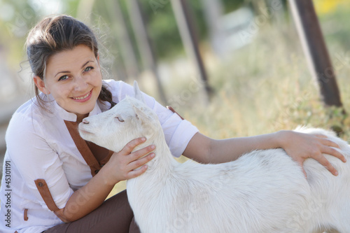 outdoor portrait of young happy woman with goat