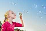 Girl making soap bubbles outside