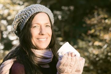 Frau mit Tasse im Herbstwald