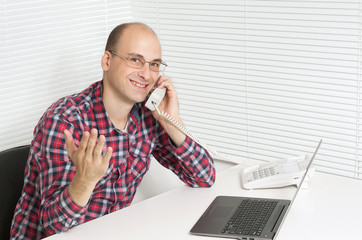 Happy young man at office, working on laptop computer, smiling.