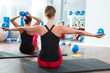 blue toning ball in women pilates class rear view