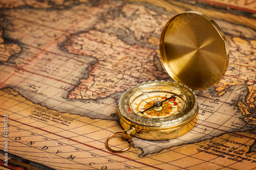 Leinwandbild Motiv Old vintage golden compass on ancient map