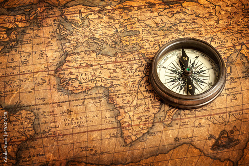 Leinwandbild Motiv Old vintage compass on ancient map