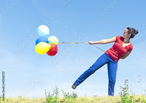Woman holding balloons in nature on the wind