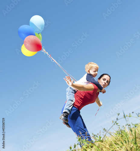 Mother and son playing with balloons in nature