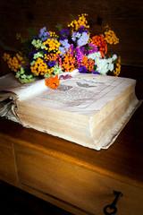 scrivania con libro antico e fiori