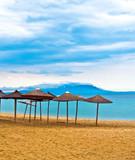 A straw umbrella on a tropical beach with blue sky