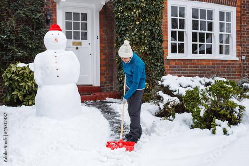 Leinwanddruck Bild Person shoveling snow