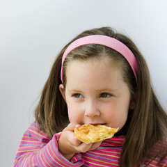 Pretty little girl eats a pancake for breakfast