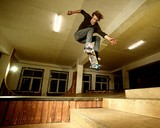 Fototapety Young man performing a stunt in a skatepark