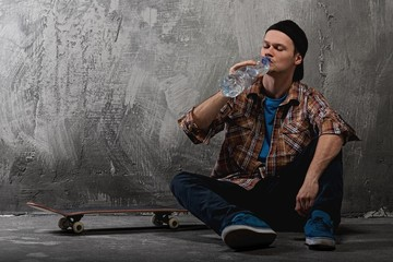 Young man with a skateboard drinking water