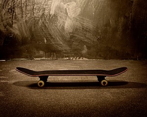 Skateboard against grunge wall