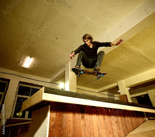 Young man performing a stunt in a skatepark