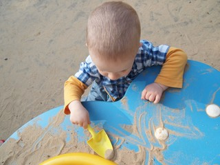 Baby playing in a sandpit