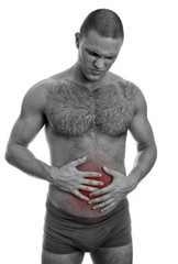 Front view of muscular man suffering from stomach pain.