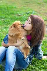 Pomeranian licking a young woman in face