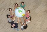 Multiracial group holding  the Earth Globe showing USA