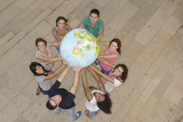 Multiracial group holding  the Earth Globe showing Africa