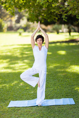 beautiful middle aged woman doing yoga outdoors
